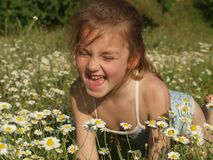 Маленькая девочка среди поля стоцвета и зеленой травы стоковое фото rf