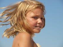 Маленькая девочка с волосами дуя в ветре стоковые фотографии rf