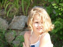 Маленькая девочка с пропуская вьющиеся волосы на предпосылке природы стоковая фотография rf
