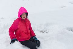 Маленькая девочка с розовыми клобуком и курткой вставая на колени в снеге стоковые фотографии rf