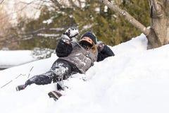Маленькая девочка одетая в одеждах зимы лежа вниз в снежном коме удерживания банка снега стоковые фотографии rf