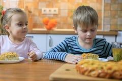 Маленькие девочки и мальчики есть домодельный яблочный пирог и выпивая сок стоковое фото rf