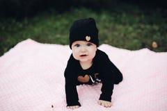 Маленький ребенок с милыми глазами лежа на розовом одеяле на земле стоковое фото