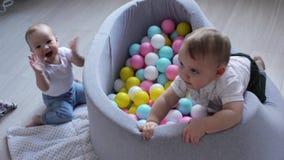 2 мальчика пробуют получить в бассейн с пластиковыми шариками акции видеоматериалы