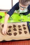 Мальчик аранжирует формы печенья отрезка вне на печь подносе На заднем плане, журнальный стол силикона и cuttersB печенья стоковые фото