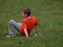 Мальчик в оранжевой футболке играя в траве стоковые фото
