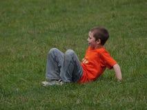 Мальчик в оранжевой футболке и джинсах играя в траве стоковые изображения rf