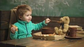 Мальчик есть пиццу на деревянной предпосылке пицца вкусная Мальчик имея кусок пиццы Принципиальная схема питания мальчик сток-видео