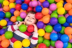 Мальчик играя в бассейне с пластиковыми шариками в питомнике Внутри помещения деятельность для детей Развитие  стоковое изображение