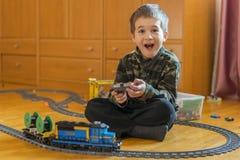 Мальчик играя с железной дорогой игрушки Мальчик играя при железная дорога лежа на поле взволнованности радостные стоковое фото rf