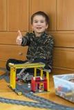 Мальчик играя с железной дорогой игрушки Мальчик играя при железная дорога лежа на поле взволнованности радостные Вертикальное фо стоковое изображение