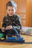Мальчик играя с железной дорогой игрушки Мальчик играя при железная дорога лежа на поле взволнованности радостные Вертикальное фо стоковое фото