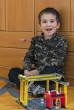 Мальчик играя с железной дорогой игрушки Мальчик играя при железная дорога лежа на поле взволнованности радостные Вертикальное фо стоковые фотографии rf