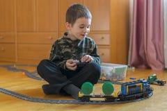 Мальчик играя с железной дорогой игрушки Мальчик играя при железная дорога лежа на поле взволнованности радостные стоковая фотография rf
