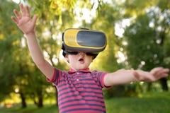 Мальчик используя шлемофон виртуальной реальности на открытом воздухе VR, стекла VR, увеличенный опыт реальности стоковые изображения rf