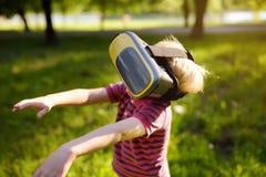 Мальчик используя шлемофон виртуальной реальности на открытом воздухе VR, стекла VR, увеличенный опыт реальности стоковое фото rf