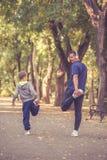 Мальчик и его отец протягивая ногу совместно в парке стоковое изображение