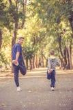 Мальчик и его отец работая совместно в парке стоковые изображения