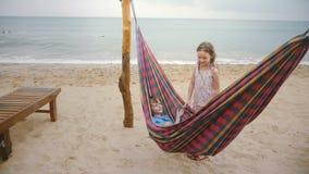 Мальчик лежа в гамаке пляжа на изумляя морском побережье, говоря с милой маленькой девочкой, братом и сестрой на каникулах видеоматериал