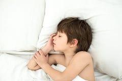 Мальчик лежит в кровати на белые постельные белья смещать ребенок стоковая фотография rf