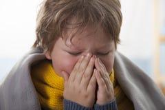 Мальчик получить холодный и дунуть ее нос дома стоковая фотография