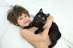 Мальчик с котом лежит в кровати на белые постельные белья стоковые изображения rf