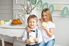 Мальчик с девушкой есть пряник пасхи на таблице праздника стоковые фото