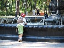 Мальчик около фонтана стоковая фотография