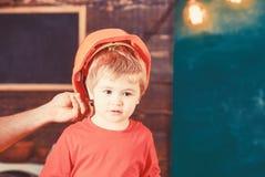 Малыш в защитной трудной шляпе, шлеме дома в мастерской Тщательно защитите ребенк с шлемом Защита и безопасность стоковые фото