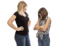 Мама кричащая на предназначенной для подростков дочери, изолированной на белой предпосылке стоковая фотография rf