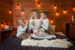 Мама с детьми в вечере зимы морозном лежа на кровати совместно стоковые фото