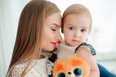 Мама обнимая и целуя его маленькую дочь стоковая фотография rf