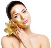Маска золота женщины, красивая модельная золотая лицевая косметика кожи, покрашенная половинная сторона, красота Skincare и обраб стоковое изображение rf