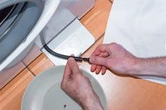 Мастер уносит обслуживание стиральной машины, очищая фильтр стоковые изображения