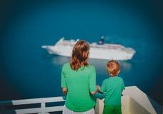 Мать и маленький сын смотря туристическое судно на море, Santorini, Греция стоковое изображение