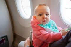 Мать и младенец сидя совместно в самолете Первый полет младенческой девушки Она изумлена стоковое изображение