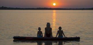 Мать и 2 дет сидят дальше на доске и взгляде затвора на заходе солнца Водные виды спорта, активный образ жизни стоковые изображения rf