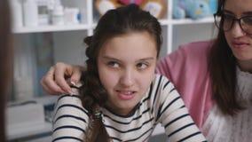 Мать и дочь на консультации на офисе доктора Портрет девочка-подростка, который нужно связывать с доктором видеоматериал