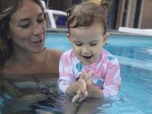 Мать наслаждаясь летним днем на бассейне с ее семьей стоковое фото rf