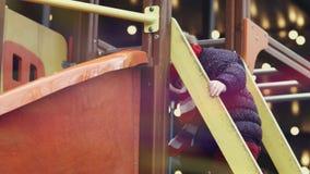 Мать помогая ее счастливой дочери, возрасту 3-4 девушки, подъем на скольжении на яркой красочной спортивной площадке акции видеоматериалы