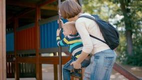 Мать помогающ и поддерживающ ее сына взобраться поляк на спортивной площадке сток-видео