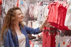Мать подготавливает для дня рождения дочери Женщина пришла к модному торговому центру выбрать одежды для дочери, но глазам стоковое изображение