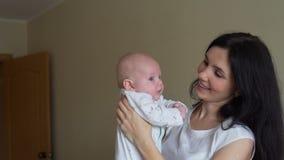 Мать поднимая меньшего младенца вверх и целуя его сток-видео