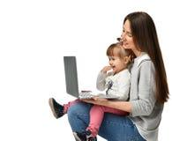 Мать семьи и дочь ребенка дома с компьтер-книжкой стоковые фотографии rf
