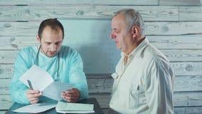 Медицина, здравоохранение и концепция людей - доктор смотрит терапию результатов и рекомендовать электрокардиограммы к senor сток-видео