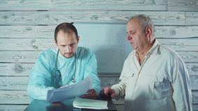 Медицина, здравоохранение и концепция людей - доктор смотрит терапию результатов и рекомендовать электрокардиограммы к senor акции видеоматериалы
