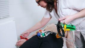 Медицинская клиника Человек получая процедуру по ECG Медсестра прикрепляет чашки всасывания вакуума и другое оборудование сток-видео