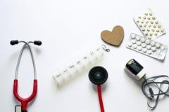 Медицинский flatlay состав на белой предпосылке Обрабатывать сердечные болезни Предохранение усложнений Оборудование искусственно стоковые изображения rf