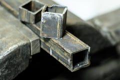металл схватывает в их зажал квадратную трубку все еще часть на верхней части Малая глубина отрезка стоковое фото rf