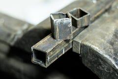 металл схватывает в их зажал квадратную трубку все еще часть на верхней части Малая глубина отрезка стоковая фотография rf